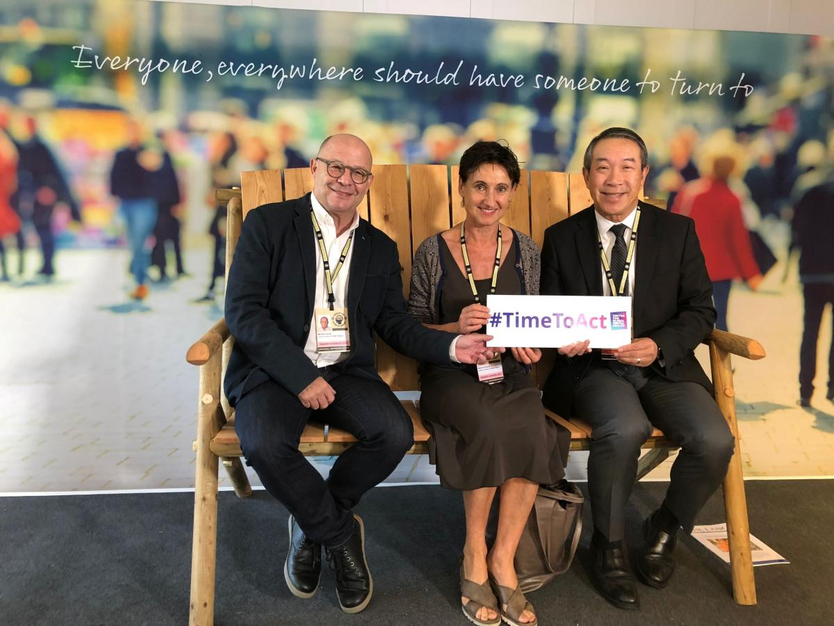 "Dr. Raymond Lam (L) and colleagues from the Belgian Ministry of Health sit on the ""Friendship Bench"", London, 9 Oct. 2018"